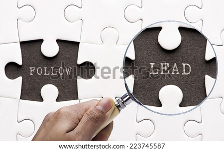 """Magnifying glass searching missing puzzle peaces """"Follow and Lead""""  - stock photo"""