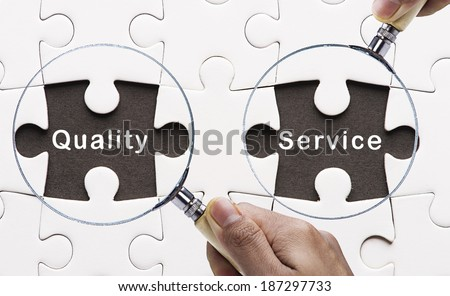 "Magnifying glass searching missing puzzle peaces ""Quality&Service"" - stock photo"