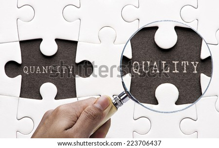 """Magnifying glass searching missing puzzle peaces """"quantity and quality"""" - stock photo"""