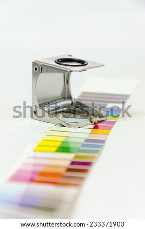 Magnifying glass standing on a leaf of the test print vertical - stock photo