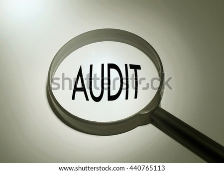 Magnifying glass with the word audit. Searching audit - stock photo