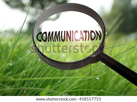 Magnifying glass with the word communication on grass background. Selective focus - stock photo