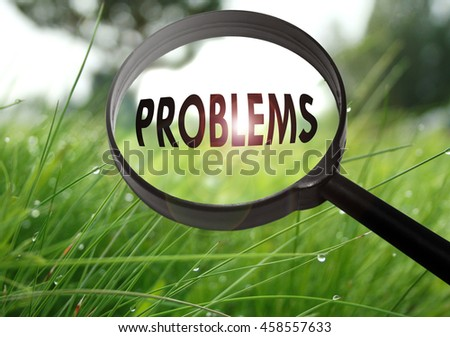 Magnifying glass with the word problems on grass background. Selective focus - stock photo