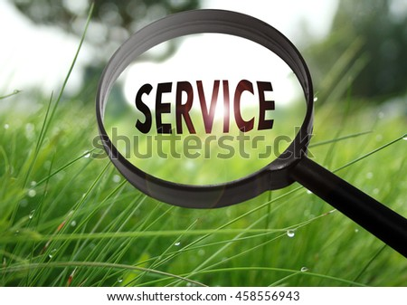 Magnifying glass with the word service on grass background. Selective focus - stock photo