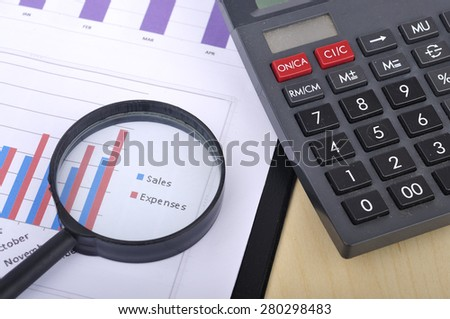 """Magnifying Glass With Yearly Graph Bar Representing """"Sales/Expenses"""" With Calculator, Selective Focus  - stock photo"""