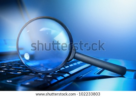 magnifying lens on the laptop keyboard in blue light - stock photo