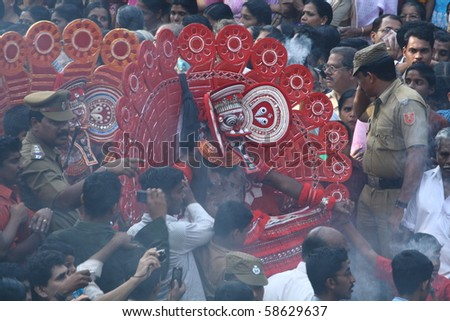 MAHE, INDIA - JANUARY 31 : Theyyam artists performing at the middle of the crowd at Palloor temple festival January 31, 2010 in Mahe, India. - stock photo