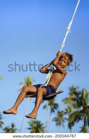 MAIGA ISLAND, SABAH, MALAYSIA - JUNE 6 : Unidentified Sea Gypsies teenager playing traditional tree swing on June 6th, 2014 in Sabah, Malaysia.  - stock photo