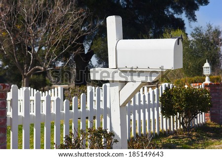 Mailbox sits in the front yard next to a white picket fence.   - stock photo