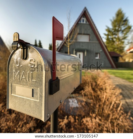 Mailbox with a house in the background. - stock photo