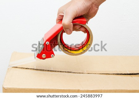 Mailing tape and box. Close up of brown cardboard box and red adhesive tape roll dispenser - stock photo