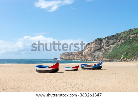 Main beach in Nazare with Traditional colorful boat on the sand - Nazare, Portugal - stock photo