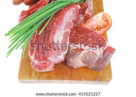 main course : fresh raw beef steak entrecote ready to prepare on cut board with green chives and tomatoes isolated on white background - stock photo