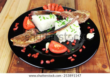 main course: grilled ribs with rice and tomatoes on black dish over wood - stock photo
