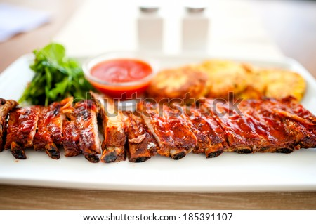 main dish - pork ribs and barbecue sauce with parsley and bread - stock photo