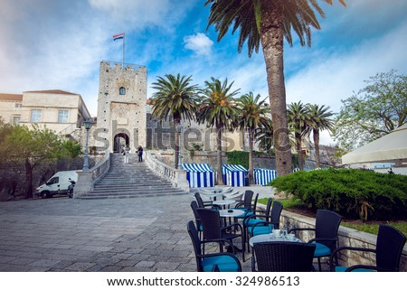Main gate of Korcula old town during day with cafe tables - stock photo