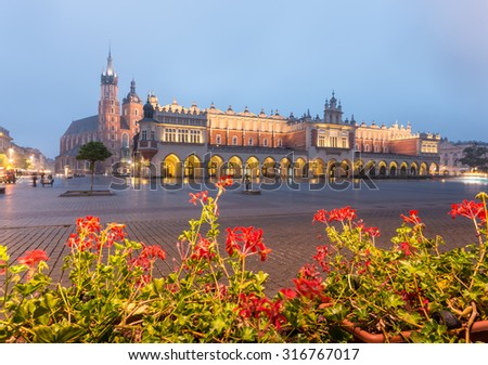 Main Market Square in Krakow, Poland, with famous Sukiennice (Cloth hall) and St Mary's church in the morning - stock photo