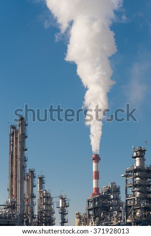 main smoking chimney of an oil refinery against blue sky - stock photo