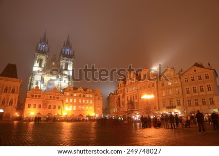 Main square of the Prague Old Town and distant Church of Our Lady before Tyn in foggy autumn night, Czech Republic - stock photo