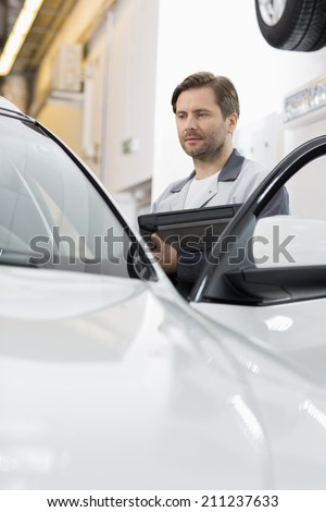 Maintenance engineer holding tablet PC while examining car in repair shop - stock photo