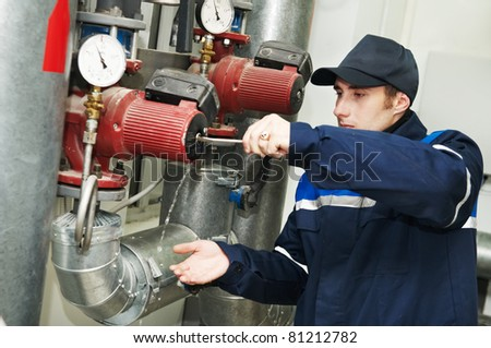 maintenance engineer repairing water pump of heating system equipment in a boiler house - stock photo