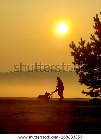 Maintenance of a golf course early in the morning. - stock photo