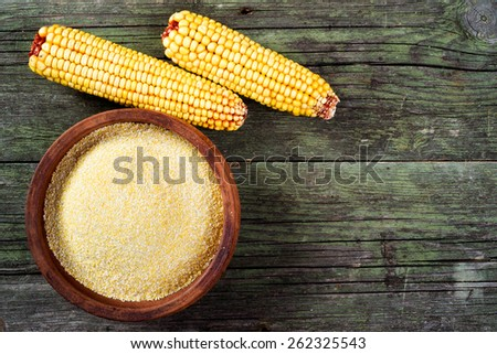 Maize, meal and ceramic bowl on wooden table - stock photo