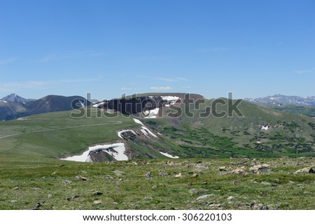 Majestic Cliffs overhang a beautiful mountaintop plateau with patches of snow that have defied the summer sun - stock photo