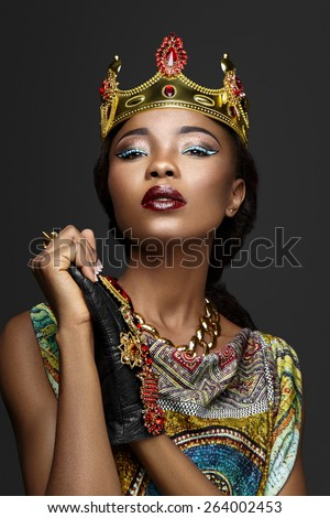 Majestic girl in a crown on a gray background - stock photo