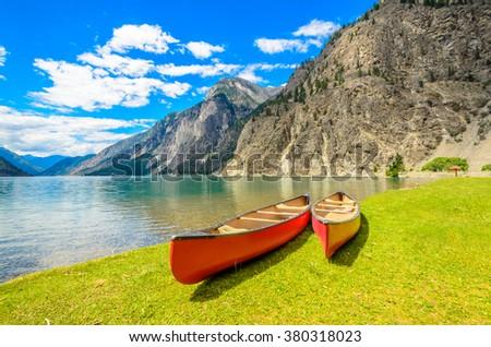 Majestic mountain lake in Canada. Seton Lake in British Columbia, Canada. Red canoe. - stock photo