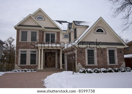 Majestic Newly Constructed Home Facade on a Blustery Winter Day - stock photo