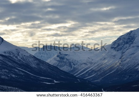 majestic snowy mountain and river landscape looking down on to the small settlement of Rundhaug, maalselv municipality - stock photo