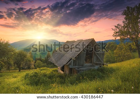 Majestic sunrise in a carpathian mountain village with old rustic house on a hill. - stock photo