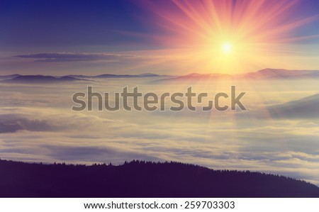 Majestic sunrise in the foggy mountain layers landscape. Soft focus filter. Filtered image: instagram toning effect. - stock photo