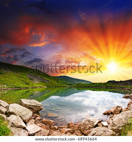 Majestic sunset in the mountains landscape over a calm lake - stock photo