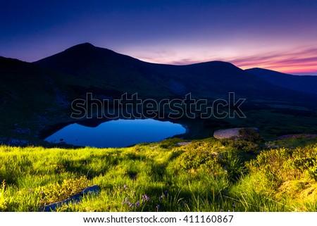 Majestic view of alpine lake illuminated lantern at twilight. Dramatic and picturesque scene. Location place National park Chornogora, Nesamovyte lake. Carpathian, Ukraine, Europe. Beauty world. - stock photo