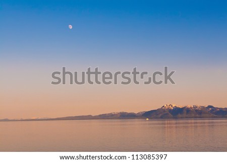 Majestic view of the moon over the Alaskan mountain range. - stock photo
