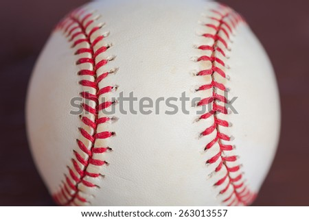 Major league baseball background with red stitches going in up and down direction.  White part of baseball is scuffed from being used.  - stock photo