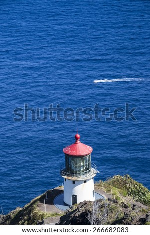 Makapuu lighthouse on a cliff in Oahu Hawaii as a boat passes. - stock photo