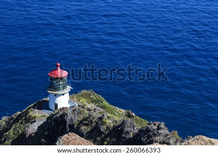 Makapuu lighthouse on a cliff in Oahu Hawaii over the beautiful blue Pacific ocean. - stock photo