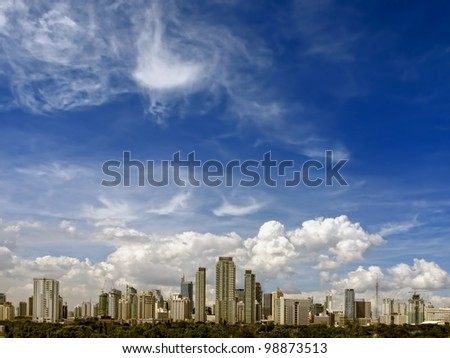 Makati skyline shot against blue sky and swirling clouds - stock photo