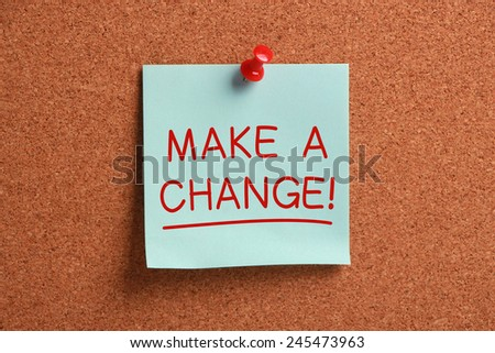 Make A Change sticky note pinned on cork. - stock photo
