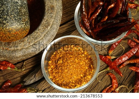 Make dry chilli to cayenne by mortar. red hot color tone - stock photo