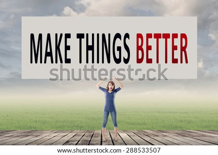 Make things better, words on blank board hold by a young girl in the outdoor. - stock photo