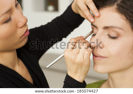 Make up artist and her model are preparing for the competition. - stock photo