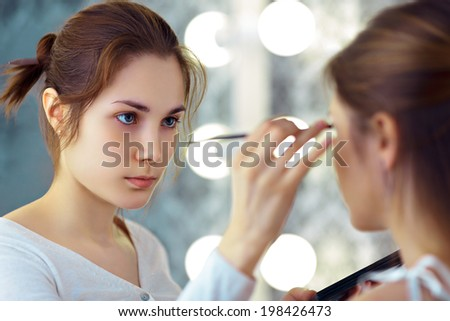 Make-up artist applying eyeshadows with a brush, selective focus on MUA  - stock photo