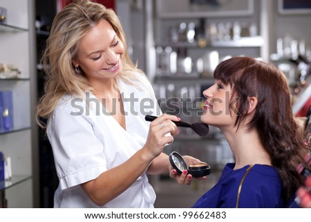 Make up artist applying face powder to a customer in a beauty store - stock photo