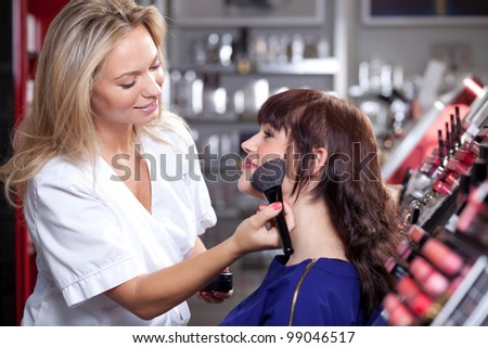 Make up artist applying face powder with a brush in a beauty store. Selective focus. - stock photo