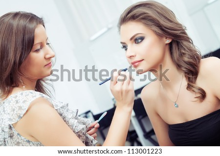 Make-up artist applying lipstick with a brush on model's lips - stock photo