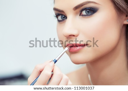 Make-up artist applying lipstick with a brush on model's lips, close-up, model looking at camera - stock photo